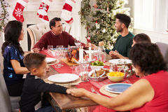 Familia con los abuelos que dicen a Grace Before Christmas Meal Fotos de archivo libres de regalías