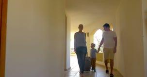 Familia con los bolsos de balanceo en pasillo del hotel almacen de video
