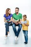 Familia con los libros de una lectura del niño Imagen de archivo