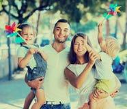 Familia con los molinoes de viento del juguete en el parque Fotografía de archivo
