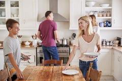 Familia con los niños adolescentes que ponen la tabla para la comida en cocina fotografía de archivo