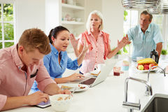 Familia con los niños adultos que tienen discusión en el desayuno Imagen de archivo libre de regalías