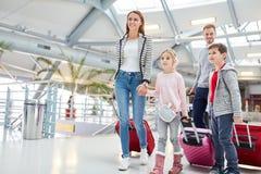 Familia con los niños en el camino al vuelo de conexión imagen de archivo