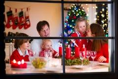 Familia con los niños en la cena de la Navidad en casa Foto de archivo libre de regalías