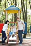 Familia con los niños en la diapositiva al aire libre. Foto de archivo libre de regalías