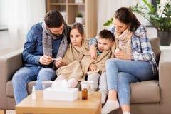 Familia con los niños enfermos que tienen fiebre en casa foto de archivo libre de regalías