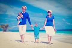 Familia con los niños que caminan en la playa tropical Fotografía de archivo