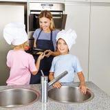 Familia con los niños que cuecen las galletas Fotografía de archivo