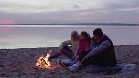 Familia con los ni?os que hablan por la hoguera en la puesta del sol almacen de video