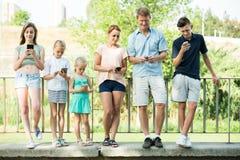 Familia con los niños que juegan con los teléfonos móviles Fotos de archivo