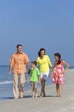 Familia con los niños que recorren divirtiéndose en la playa Foto de archivo libre de regalías