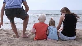 Familia con los niños que se sientan en la playa por el mar almacen de metraje de vídeo