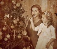 Familia con los niños que visten el árbol de navidad Fotografía de archivo libre de regalías