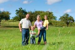Familia con los niños y balompié en un prado Fotos de archivo