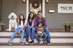 Familia con los niños y el perro casero Sit On Steps Of Home fotografía de archivo
