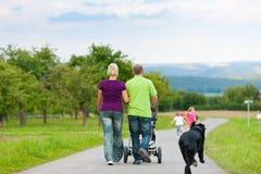 Familia con los niños y el perro que tienen caminata Imagen de archivo libre de regalías