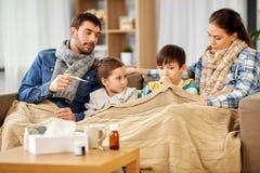 Familia con los ni?os enfermos que tienen fiebre en casa fotografía de archivo