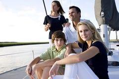 Familia con los niños adolescentes que se sientan en el barco Imagen de archivo libre de regalías
