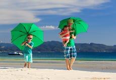 Familia con los paraguas en vacaciones tropicales de la playa Imagen de archivo