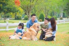 Familia con los perros que se sientan en el parque foto de archivo