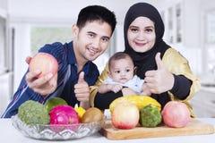 Familia con los pulgares-para arriba y las frutas en casa Foto de archivo libre de regalías
