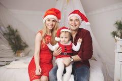 Familia con los sombreros de santa en casa Fotos de archivo