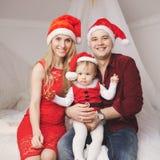 Familia con los sombreros de santa en casa Imagen de archivo libre de regalías