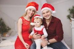 Familia con los sombreros de santa en casa Fotografía de archivo libre de regalías