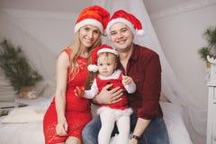 Familia con los sombreros de santa en casa Imágenes de archivo libres de regalías