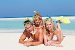 Familia con los tubos respiradores que disfruta de día de fiesta de la playa