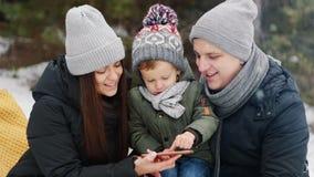 Familia con miradas del hijo en la foto en el teléfono en Navidad feliz del bosque del invierno almacen de metraje de vídeo