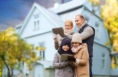 Familia con PC de la tableta sobre casa viva en otoño imagenes de archivo