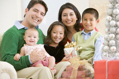 Familia con recién nacido, sentándose en el sofá, sosteniendo Prese Fotos de archivo libres de regalías