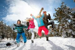 Familia con salto de altura de los niños el día de invierno el vacaciones del esquí y Fotos de archivo
