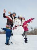 Familia con un muñeco de nieve Fotografía de archivo libre de regalías