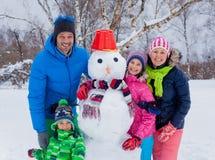 Familia con un muñeco de nieve imagenes de archivo