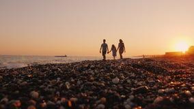 Familia con un niño que camina en la puesta del sol en la costa, relajándose junto en un centro turístico almacen de video