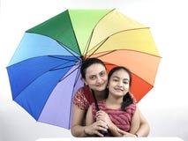 Familia con un paraguas del arco iris Fotos de archivo