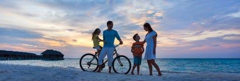 Familia con una bici en la playa tropical foto de archivo libre de regalías