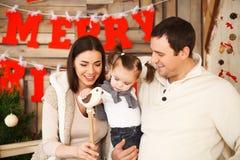 Familia con una hija del año cerca del fondo de la Navidad Fotos de archivo libres de regalías