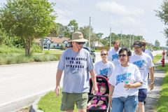 Familia con una parada infantil participar en un paseo católico de la caridad de la comunidad foto de archivo