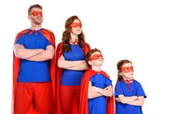 familia confiada de super héroes en los trajes que se colocan con los brazos cruzados y que miran lejos imagenes de archivo