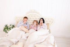 Familia conseguida enferma, estornudo, y mentira en cama en casa Foto de archivo