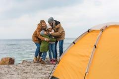 familia de abarcamiento feliz que tiene acampar Foto de archivo
