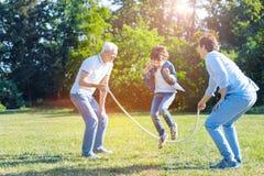 Familia de apoyo que juega con la comba en parque Fotografía de archivo libre de regalías