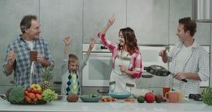 Familia de baile en una cocina moderna mientras que prepara la comida, gasto hermoso del tiempo junta almacen de video
