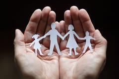 Familia de cadena de papel protegida en manos ahuecadas Fotos de archivo