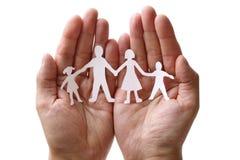 Familia de cadena de papel protegida en manos ahuecadas Foto de archivo libre de regalías
