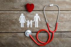 Familia de cadena roja del corazón, del estetoscopio y del papel en la tabla de madera Imagenes de archivo