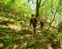 Familia de caminantes que caminan en un rastro de montaña Imagenes de archivo